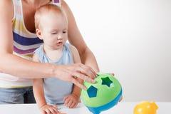 La mamá enseña al bebé a poner los juguetes Lanzamiento del estudio imagen de archivo libre de regalías