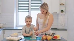 La mamá enseña al hijo a frotar el queso Una madre hermosa joven con en la camisa blanca y el cocinero lindo del hijo en una coci almacen de video