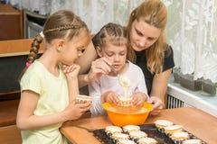 La mamá enseña a dos hijas a cocinar a Easter Fotos de archivo