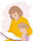 La mamá enseña a la hija a leer Imágenes de archivo libres de regalías