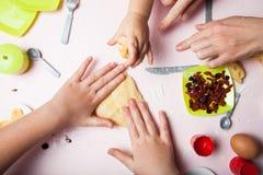 La mamá enseña los niños jovenes a cómo cocinar Las manos amasan la pasta, los utensilios de los niños foto de archivo