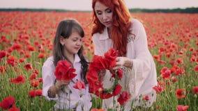 La mamá enseña a la pequeña hija a tejer la guirnalda de flores en campo de florecimiento de la amapola en la puesta del sol metrajes