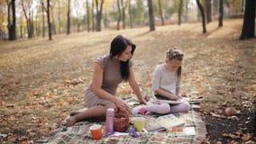 La mamá enseña a su hija a escribir con la tiza en letras de una pizarra, el alfabeto Familia feliz al aire libre Madre y almacen de video