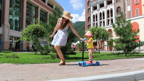 La mamá enseña a un niño a montar una vespa en un parque al día de verano soleado HD lleno 1920x1080 almacen de metraje de vídeo