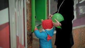 La mamá enseña a un niño a utilizar un cajero automático almacen de video