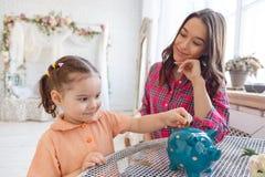 La mamá enseña a una pequeña hija a recoger el dinero en una hucha imagen de archivo