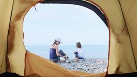 La mamá está construyendo una torre de piedras con su poca hija en la playa del mar almacen de metraje de vídeo