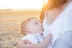 La mamá está cuidando a su niño en naturaleza Imagen de archivo libre de regalías