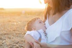 La mamá está cuidando a su niño en naturaleza Fotos de archivo libres de regalías