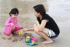 La mamá está jugando con el niño en la playa Foto de archivo libre de regalías