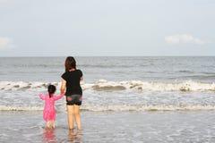 La mamá está jugando con el niño en la playa Imagen de archivo libre de regalías
