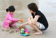 La mamá está jugando con el niño en la playa Foto de archivo