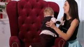 La mamá feliz besa a su pequeño hijo querido en casa que se sienta en una silla suave almacen de metraje de vídeo