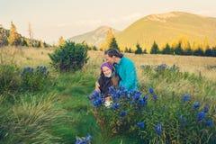 La mamá feliz con la hija adolescente se sienta en prado alpino Foto de archivo libre de regalías