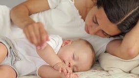 La mamá feliz está mintiendo con su bebé durmiente recién nacido en cama, ella admira al bebé almacen de metraje de vídeo