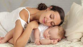 La mamá feliz está mintiendo con su bebé durmiente recién nacido en cama, ella admira al bebé almacen de video