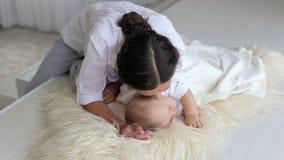 La mamá feliz está mintiendo con su bebé durmiente recién nacido en cama, lo besa suavemente almacen de metraje de vídeo