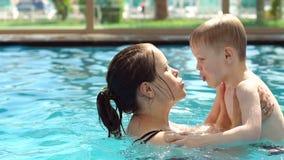 La mamá feliz está nadando en la piscina con su pequeño hijo y lo está besando almacen de metraje de vídeo