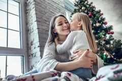 La mamá feliz felicita al niño con una Feliz Año Nuevo y una Navidad imagen de archivo libre de regalías