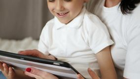 La mamá feliz y su niño pasan tiempo en la tableta en casa, jugando y mirando las historietas, jugando a los videojuegos, usando almacen de video