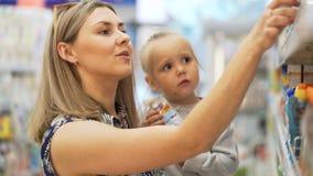 La mamá habla con la hija, buscando productos del ` s del niño cerca para arriba almacen de video