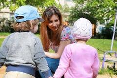 La mamá habla con los gemelos de los niños y les enseña a cómo actuar fotografía de archivo libre de regalías