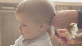 La mamá hace la cola de su pequeño pelo del ` s de la hija, se peina el pelo a una pequeña muchacha de tres años, muchacha con el almacen de video