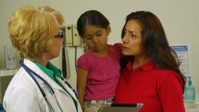 La mamá hispánica con la hija escucha el pediatra almacen de video