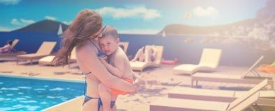 La mamá joven de la bandera que detiene a un bebé que se relaja por la piscina brilla el viaje brillante de las vacaciones de fam fotos de archivo libres de regalías