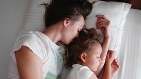 La mamá joven está durmiendo con su pequeña hija linda almacen de metraje de vídeo