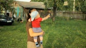La mamá juega con el bebé en un jardín hermoso con las pinzas Bebé adorable menos que un año metrajes