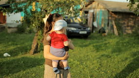 La mamá juega con el bebé en un jardín hermoso con las pinzas Bebé adorable menos que un año almacen de metraje de vídeo
