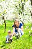 La mamá juega con el pequeño hijo en la hierba fotografía de archivo