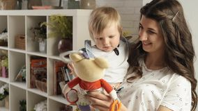 La mamá juega con su bebé con la cámara lenta brillante de la muñeca de trapo almacen de video