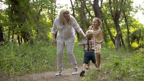 La mamá juega con su hija e hijo en el parque almacen de video