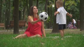 La mamá juega con su hijo con una bola almacen de video