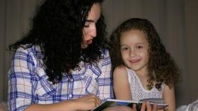 La mamá, junto con una pequeña hija hermosa, lee con una torsión de un cuento de hadas para la noche, hundido en la historia de almacen de video