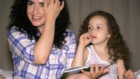 La mamá, junto con una pequeña hija hermosa, lee con una torsión de un cuento de hadas para la noche, hundido en la historia de metrajes