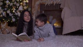 La mamá lee un libro a su hijo y lo besa que miente en el piso cerca del árbol de navidad el día de la Navidad 4K almacen de video