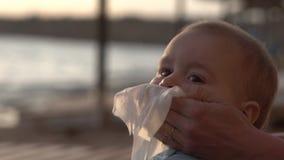 La mamá limpió la nariz de su bebé con una servilleta en la cámara lenta almacen de metraje de vídeo