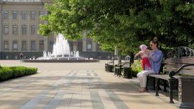 La mamá linda joven con su hija pequeña se sienta en banco en callejón en parque de la ciudad con los árboles y la fuente
