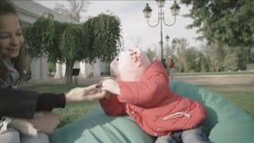 La mamá lleva a cabo la mano del ` s del bebé Madre y sus pequeñas hijas adentro al aire libre metrajes