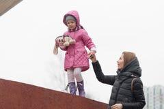 La mamá lleva a la hija a mano con un obstáculo imagen de archivo