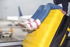 La mamá lleva su equipaje con el bebé en el terminal de aeropuerto imagen de archivo