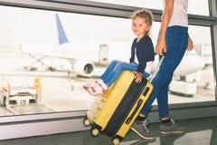 La mamá lleva su equipaje con el bebé feliz en el terminal de aeropuerto Imagen de archivo libre de regalías