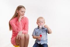 La mamá mira a su hijo para soplar burbujas Imagenes de archivo