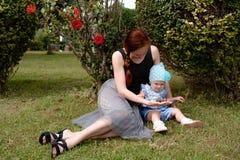 La mamá muestra los conos del árbol de la hija que se sientan en el césped en el parque fotos de archivo