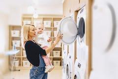 La mamá muestra a su hija una lavadora foto de archivo libre de regalías