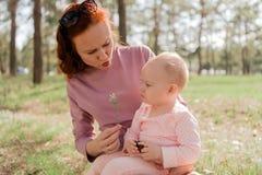 La mamá muestra a su hija una rama de árbol en el parque imagenes de archivo