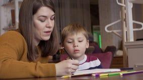 La mamá muestra a su hijo curioso lindo cómo dibujar animales correctamente almacen de video